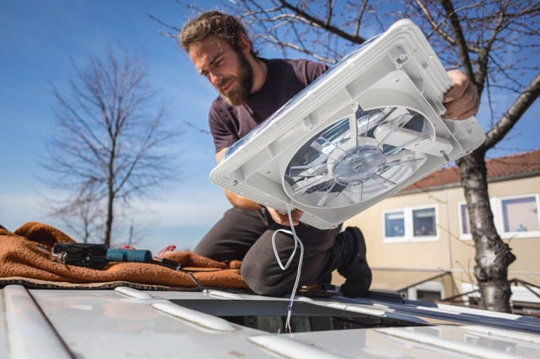 Man instaill one of the best roof vent fans for vans.