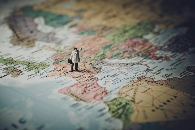Tiny figure of a human standing on a map