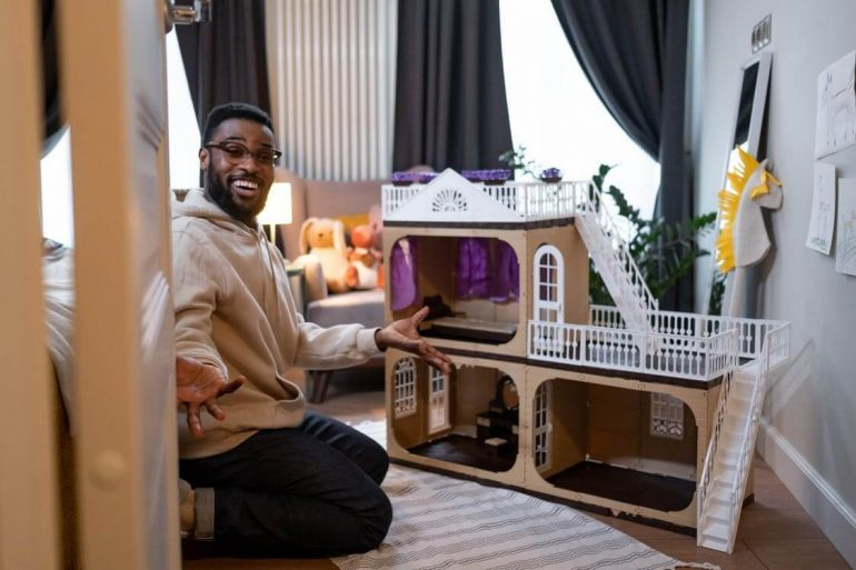 A man planning the size of a house with a cardboard house