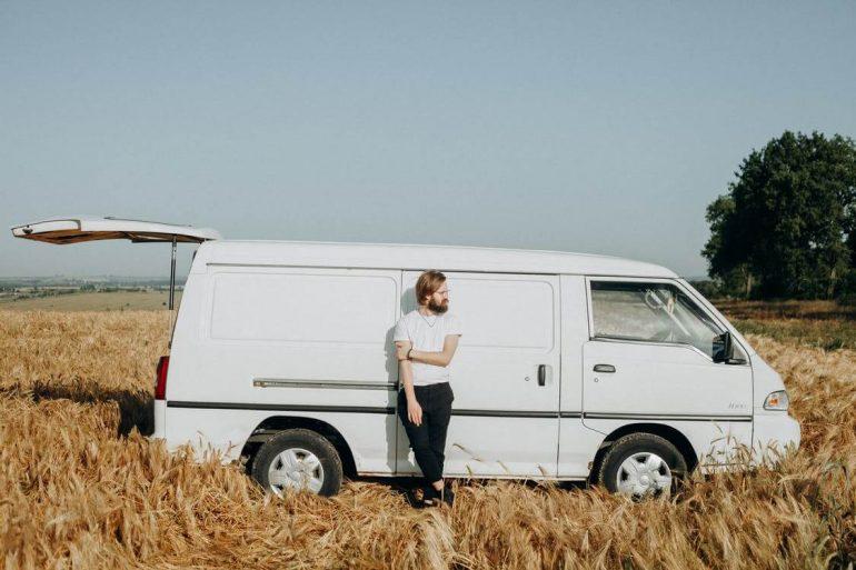 Van life - a man standing in front of white van