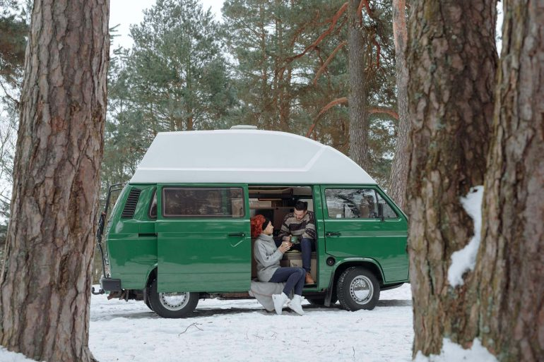 A van with a couple sitting inside, parked in the woods