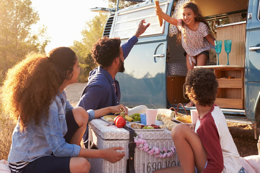 Family eating food outside their van