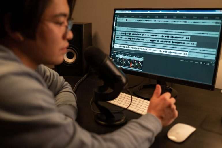 A podcaster working at a digital audio workstation.