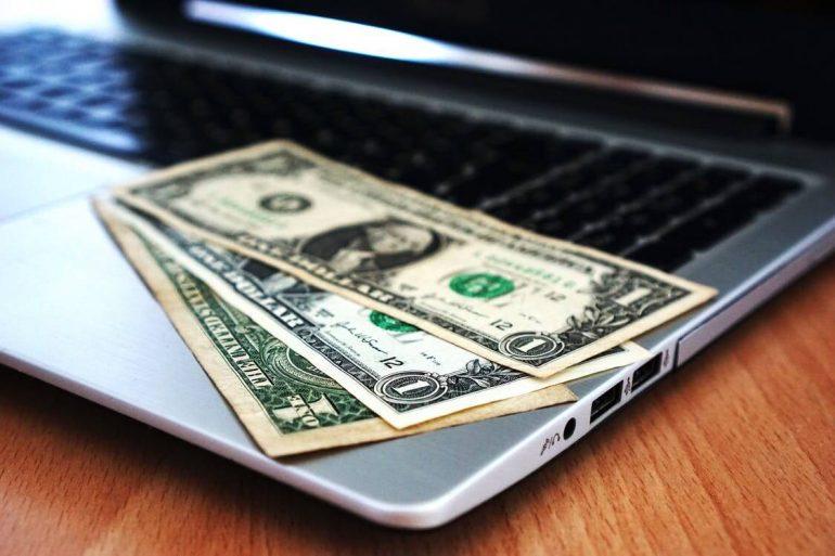 Three dollar banknotes on laptop.