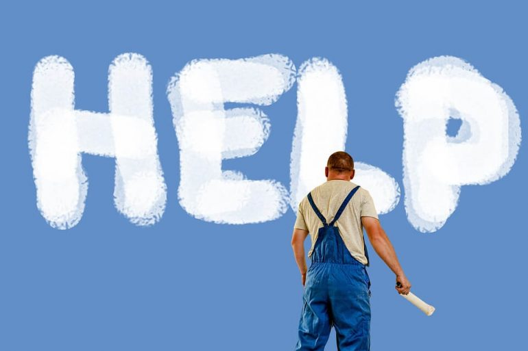 A man in front of a blue wall with HELP written on it.