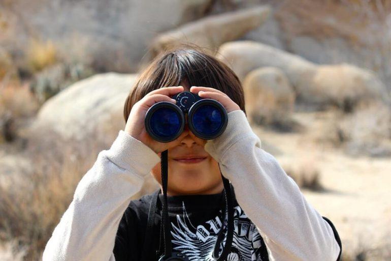 A kid looking through binoculars.