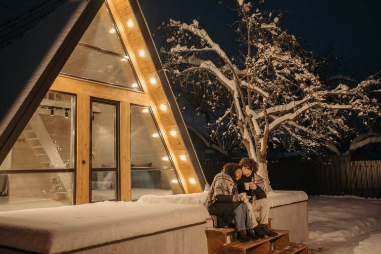 A couple sitting in front of a tiny home