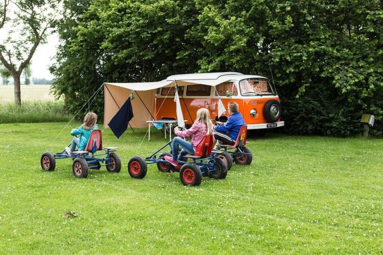 Van parked in a field and little kids riding bikes