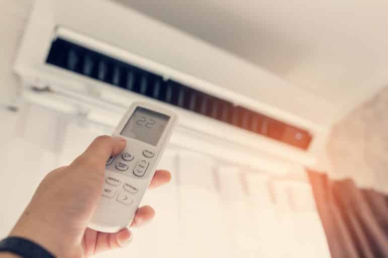 A person holding a remote for an air conditioner