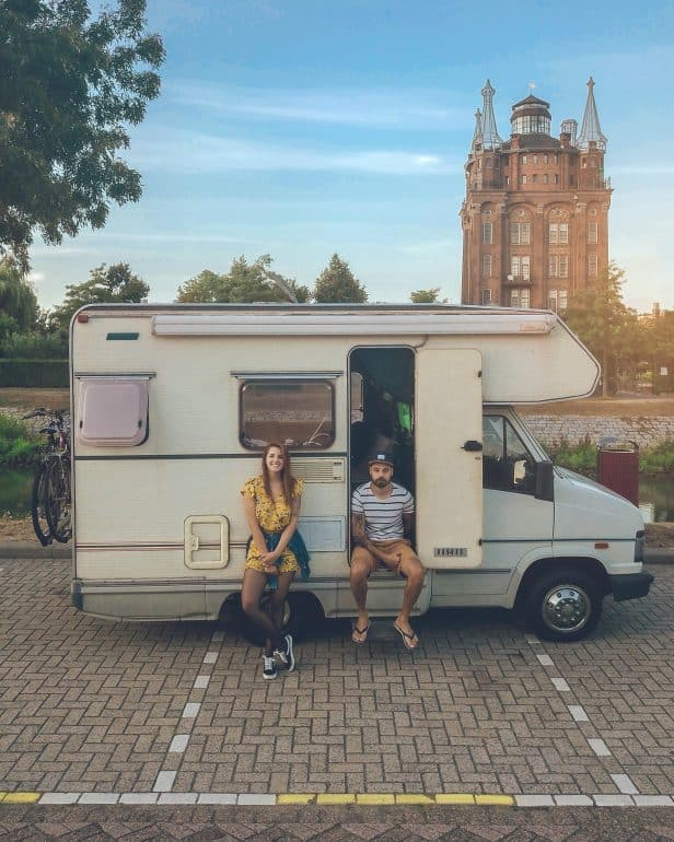 A couple sitting in front of a van