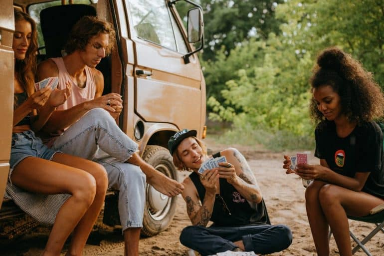 group of friends sitting outside of a camper van