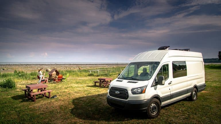 a van parked in a field near some people and benches