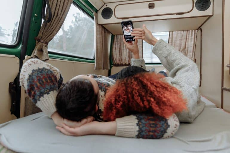 two people looking at a phone in the back of a van