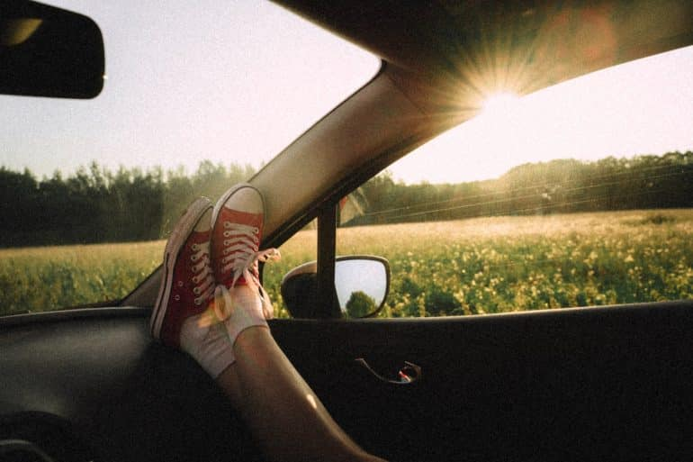 a woman with her feet on the dashboard