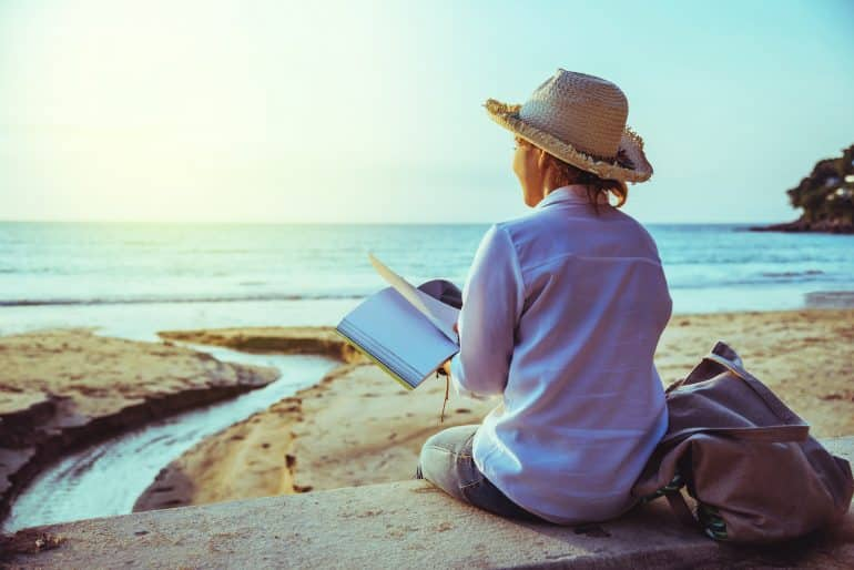 a woman sitting on a beach and writing in a notebook